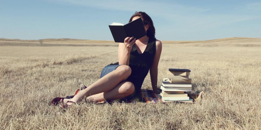 Woman reading books in an open field